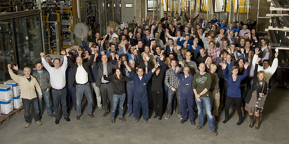A group photo of all MHB employees inside the factory, cheering